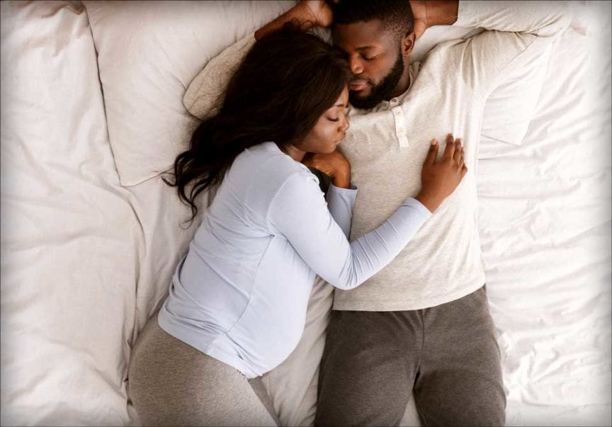 A couple lays on the bed together. The woman is pregnant.